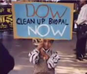 picture of young boy carrying sign that says 'Dow clean up Bhopal NOW'; click to go to video page; opens in new window
